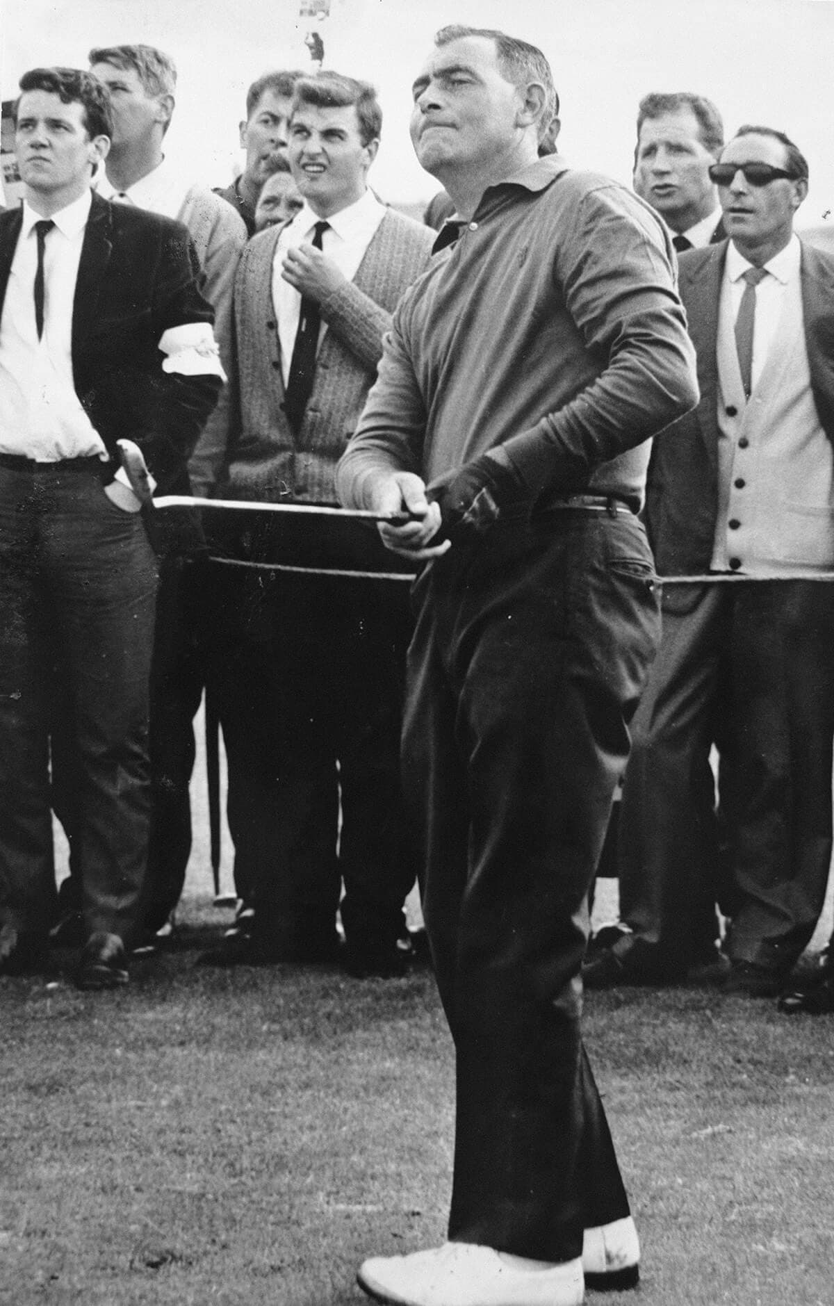 Christy O'Connor playing from the fairway. In background F J Sharpe.